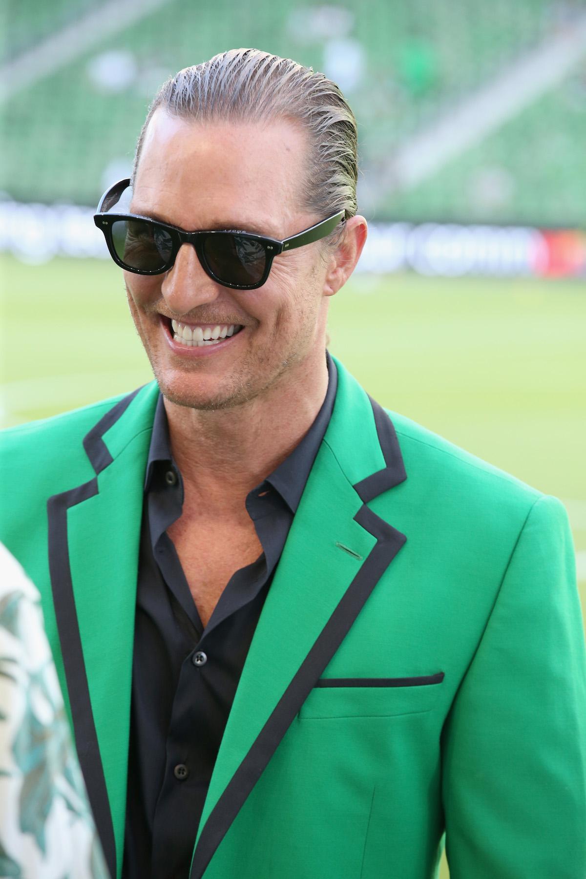Matthew McConaughey wearing a green blazer and sunglasses smiling