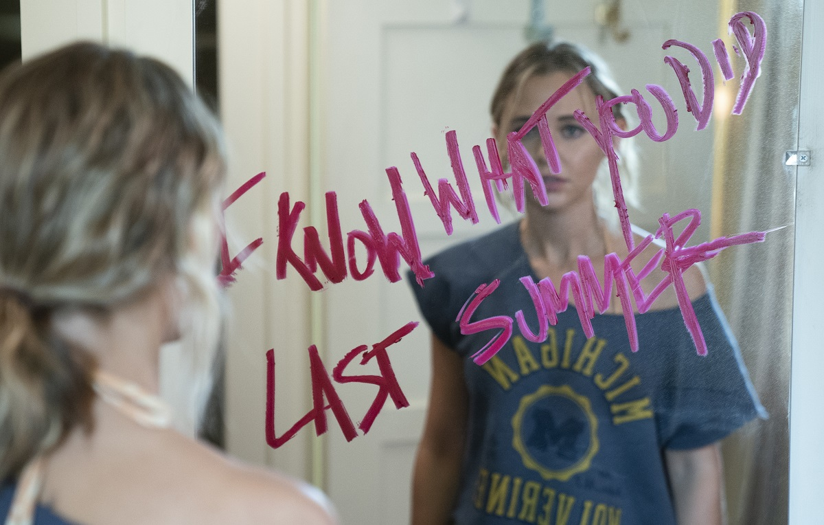 """Madison Iseman stands in front of a mirror with """"I Know What You Did Last Summer"""" written in pink lipstick for the remake of the 1997 horror movie."""