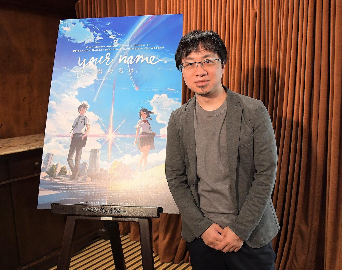 Makoto Shinkai poses next to a poster for his film 'Your Name'