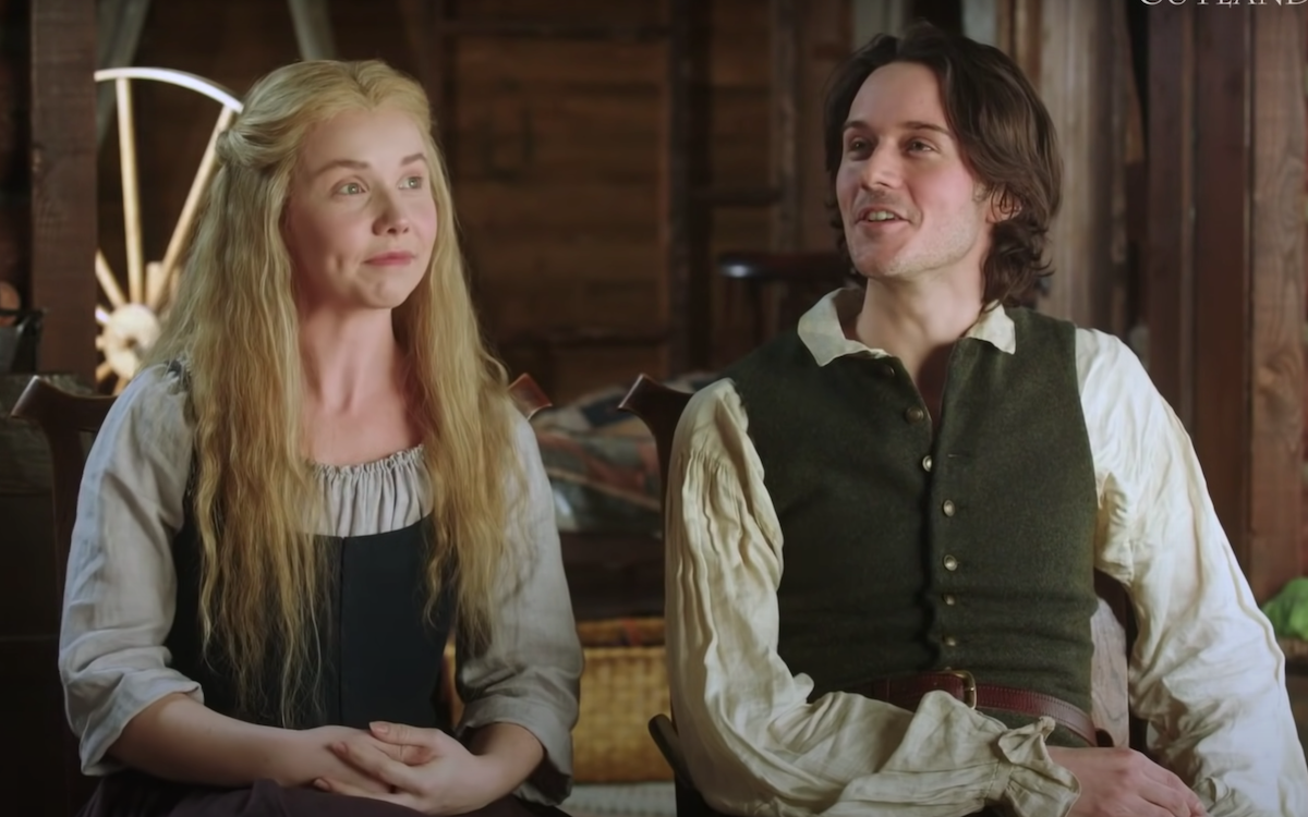 Lauren Lyle and César Domboy dressed as 'Outlander's Marsali and Fergus in a promotional video for 'Outlander' Season 6. Lauren sits on the left in a green colonial dress with a beige quarter-sleeve top underneath. Her long blonde hair is down in front of her shoulders. Domboy sits on the right wearing a tan colonial shirt and green vest with gold buttons and a brown leather belt. They sit inside in a log cabin. Marsali and Fergus' newest son, Henri Christian, could have a big plot in the upcoming 'Outlander' Season 6.