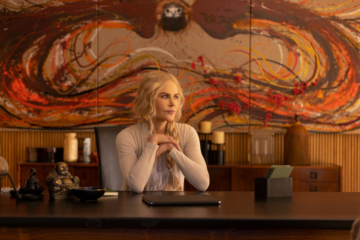 Nicole Kidman as Masha in Hulu's Nine Perfect Strangers. She's sitting at a desk with her hands clasped together, and she's looking sideways thinking. Fans have more than 1 theory about who's threatening her.