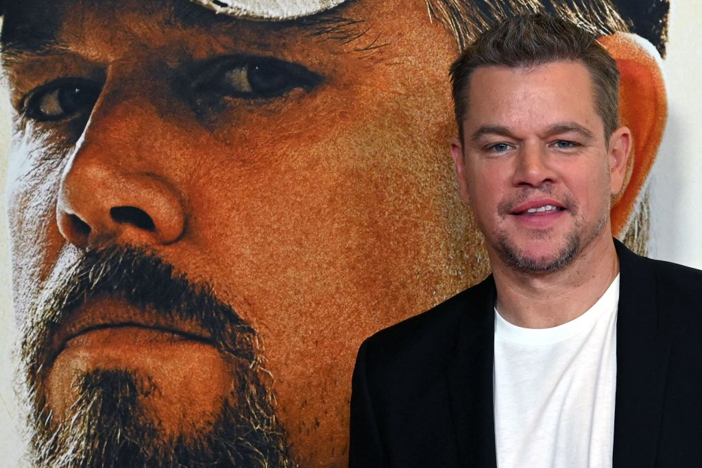 Matt Damon poses in front of a 'Stillwater' photo. He's wearing a black suit and white shirt.