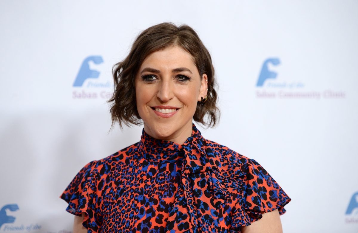 Mayim Bialik in an orange and blue patterned dress.