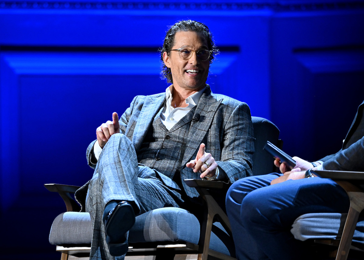Matthew McConaughey in a plaid suit smiling and sitting in a chair on a stage
