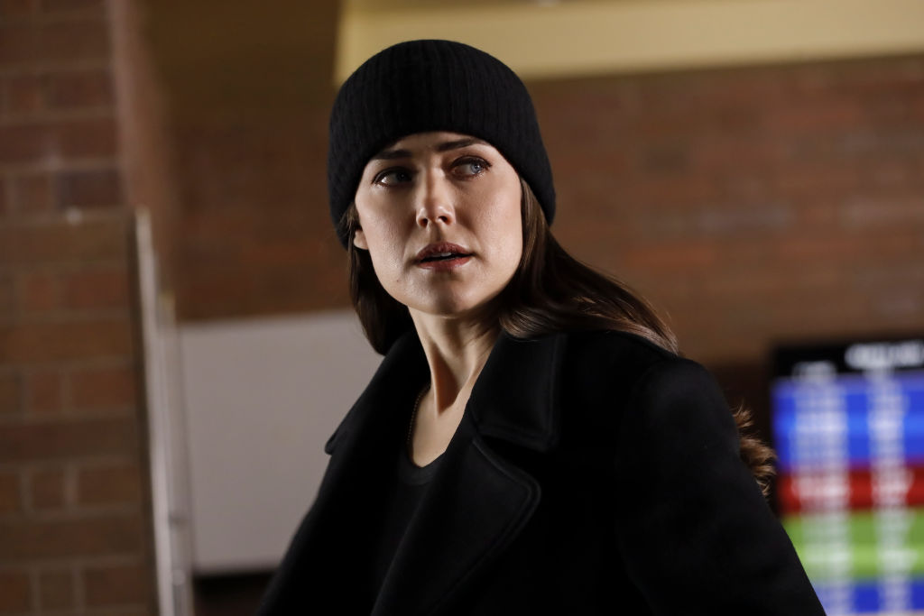 Megan Boone as Liz Keen. She's dressed in all black with a black cap as she looks over her shoulder.