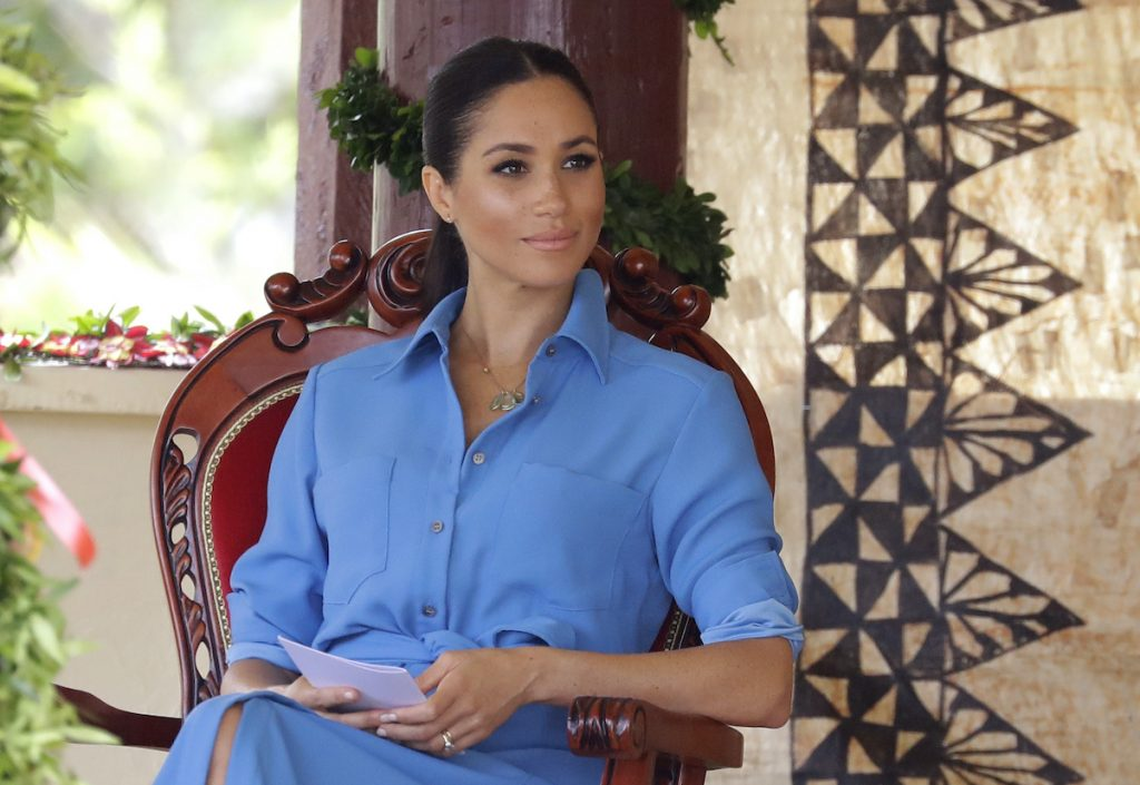 Meghan Markle sitting, staring in the distance