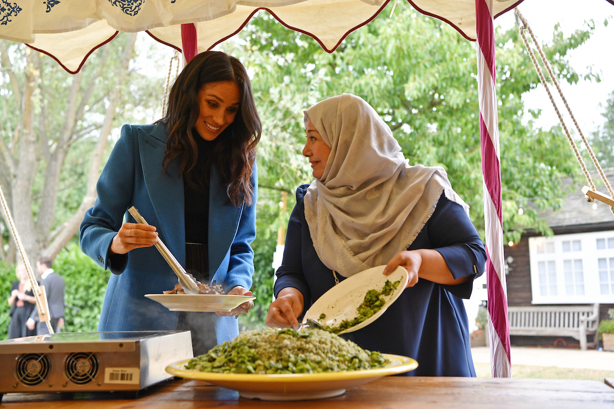 Meghan Markle in a blue blazer plating food with tongs while speaking with a woman