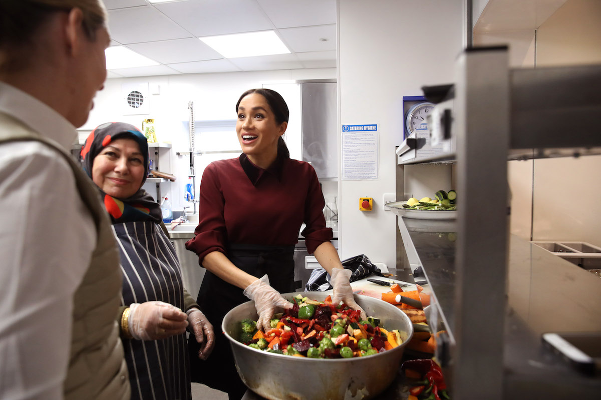Meghan Markle smiles as she prepares food wearing rubber gloves at the Hubb Community Kitchen in 2018