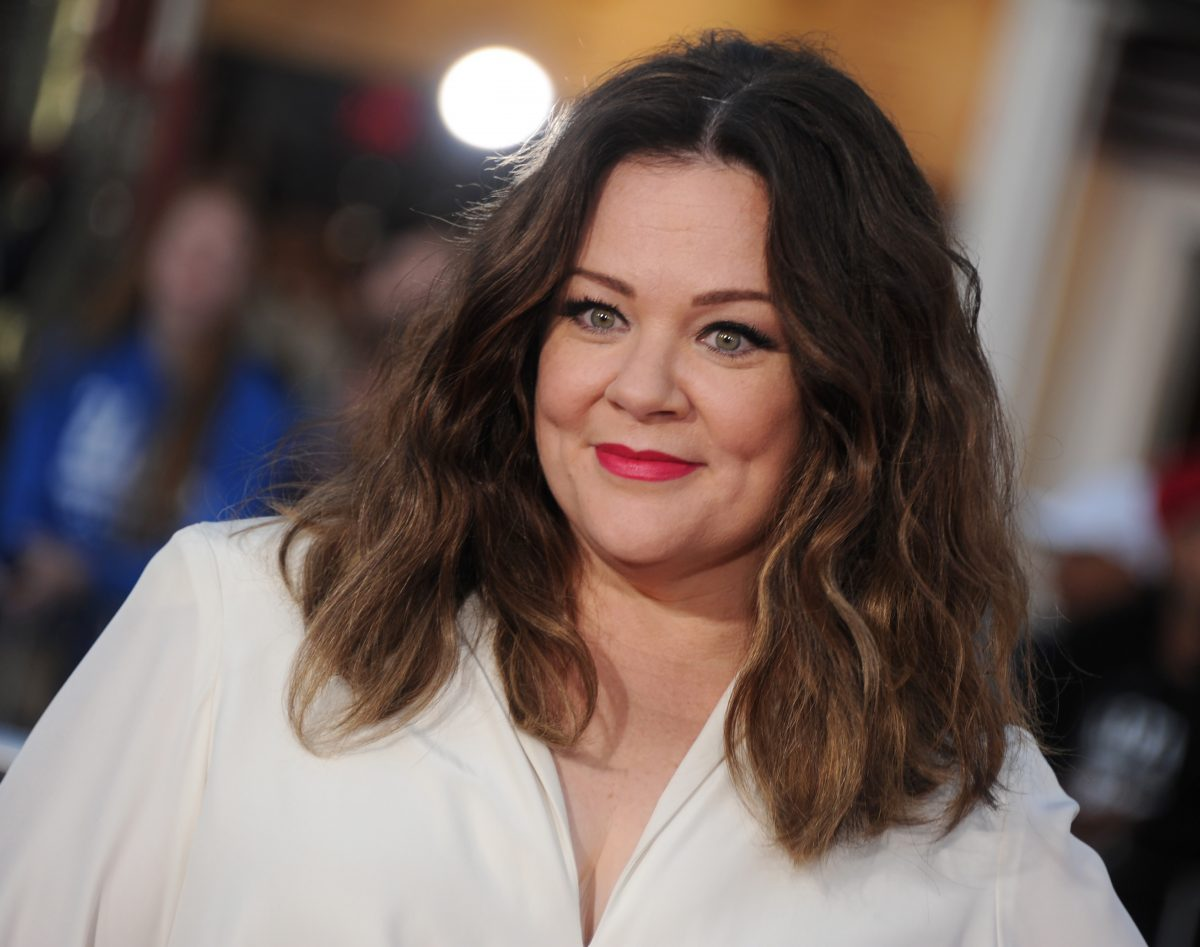 Melissa McCarthy in a white top wearing her wavy, brown hair parted down the middle.
