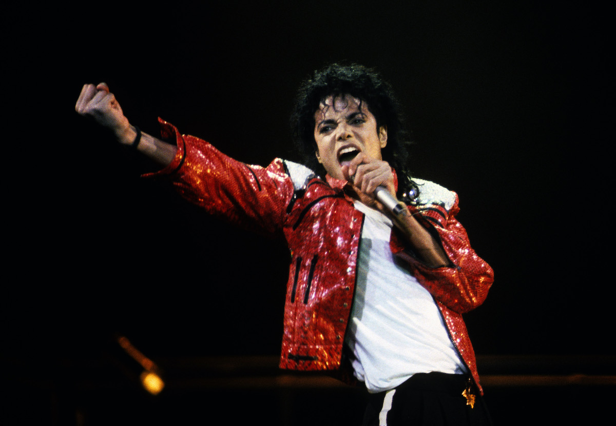 Michael Jackson wears a red jacket and performs in concert