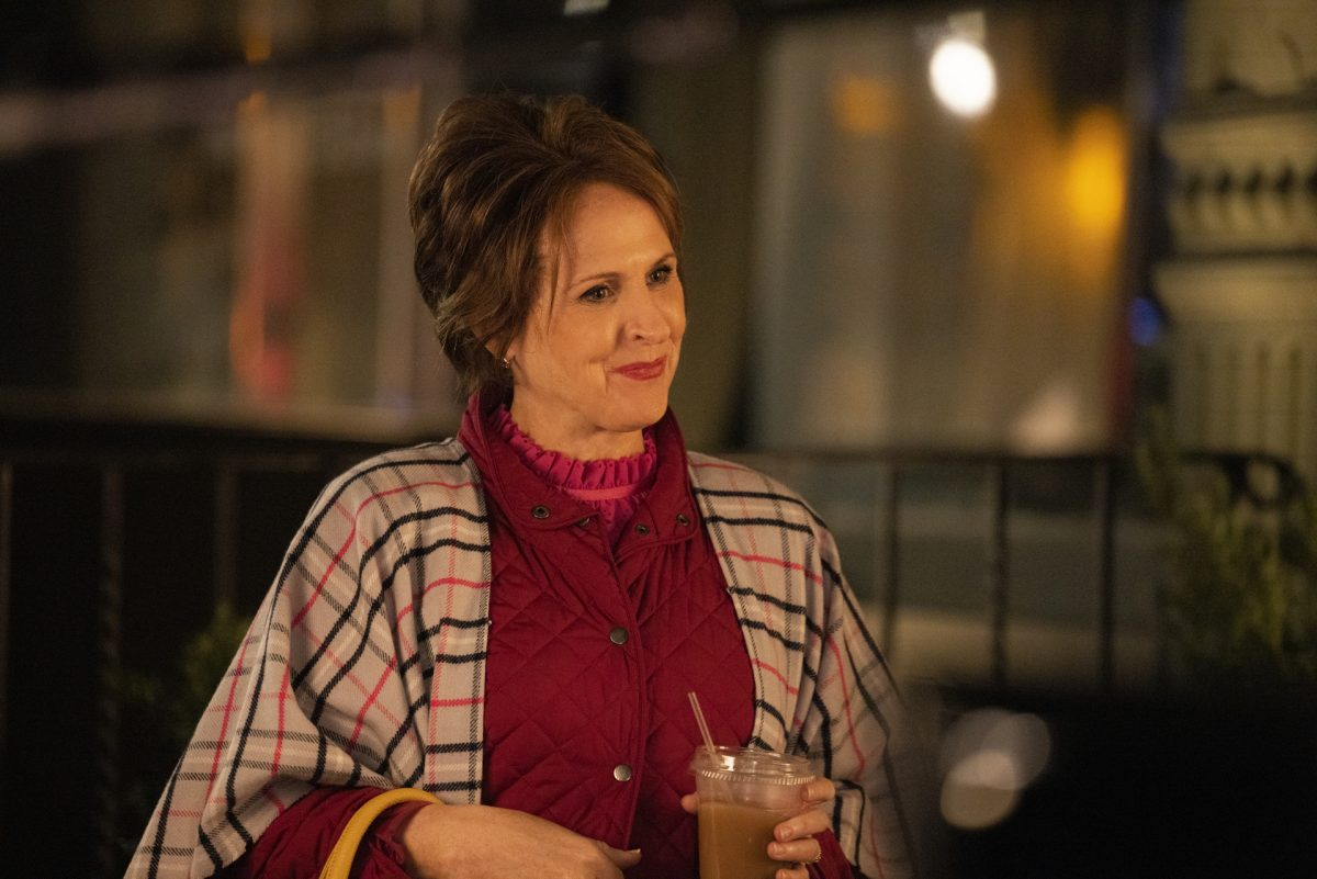 Molly Shannon wears a pink coat and plaid cape in 'The Other Two.'