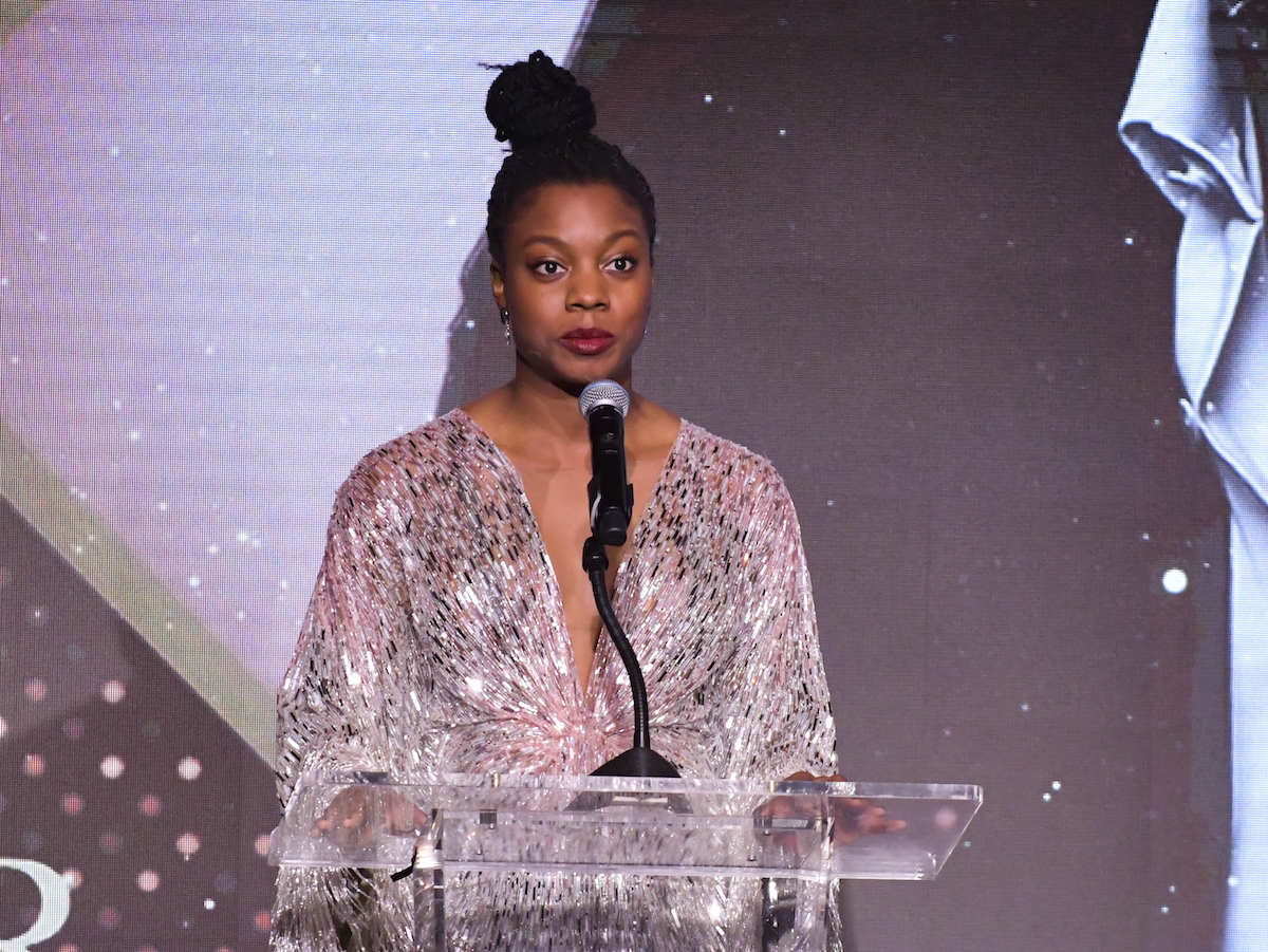 Nia DaCosta, director of 'Candyman,' in a shimmery gold dress at The African American Film Critics Association's 11th Annual AAFCA Awards.