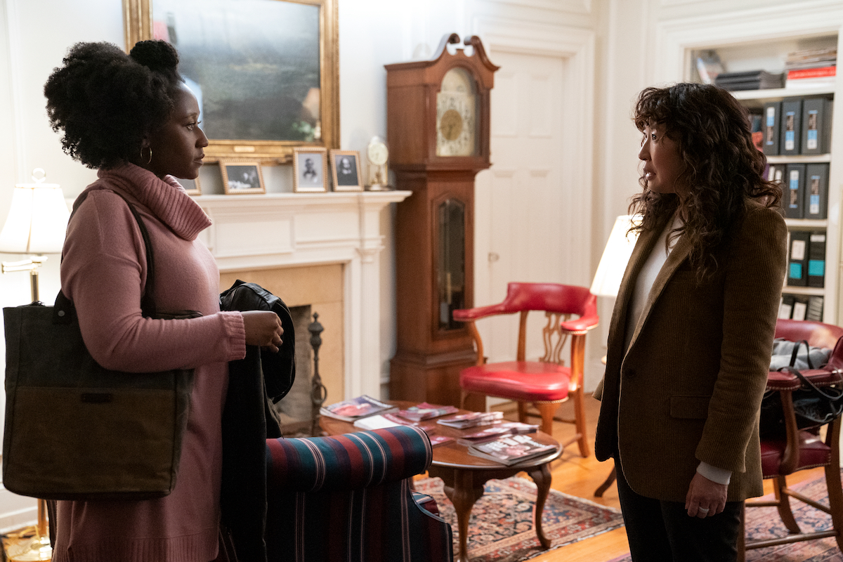Nana Mensah wears a pink turtleneck sweater as she stands across from Sandra Oh in a brown suit in 'The Chair' Season 1