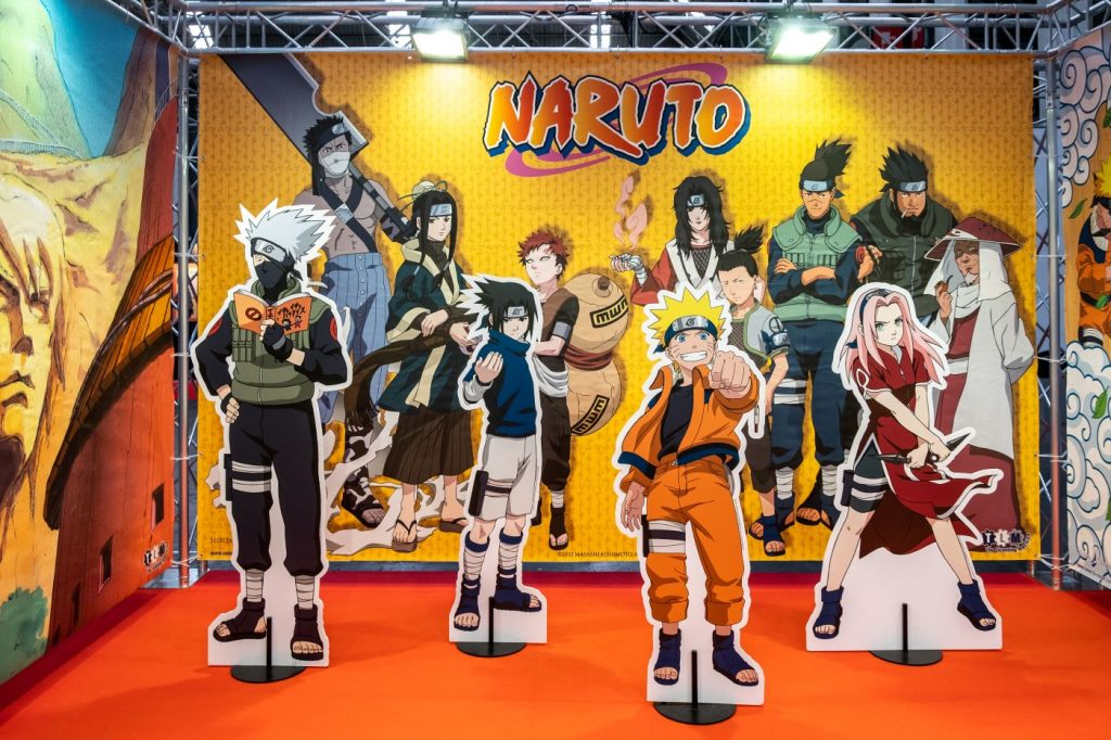 'Naruto' character cardboard cutouts in front of a background of more 'Naruto' characters.