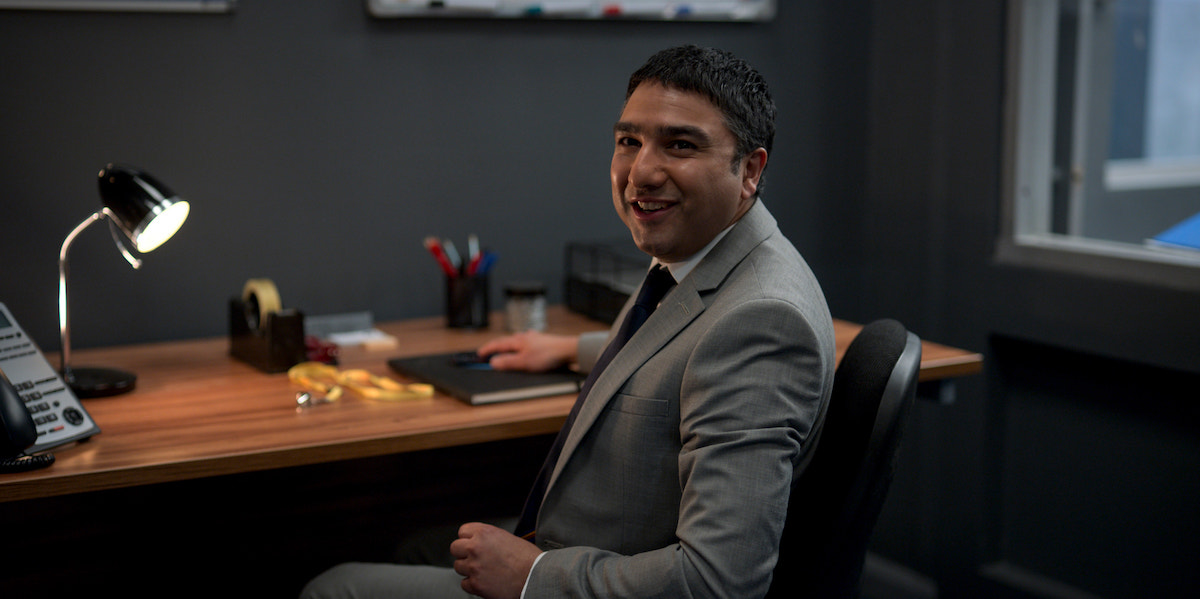 Nick Mohammed smiles as he sits at a desk wearing a suit and tie as Nathan Shelley in 'Ted Lasso' Season 2