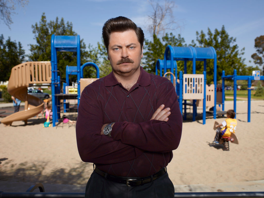 Nick Offerman as Ron Swanson stands in front of the park wearing a burgundy sweater with his arms crossed and a stern look on his face.