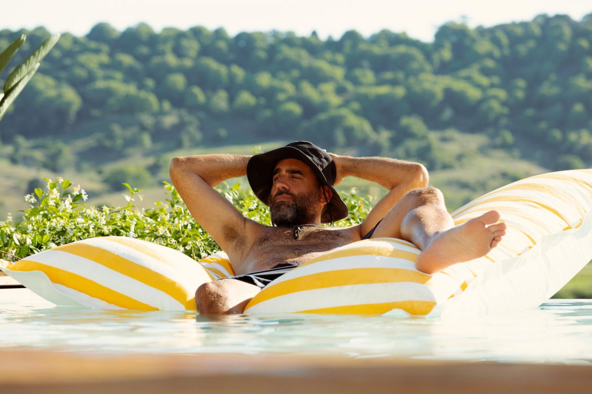 Bobby Cannavale as Tony Hogburn on Hulu's 'Nine Perfect Strangers.' He's lying on a yellow and white striped float in the pool and has a dark sun hat on.