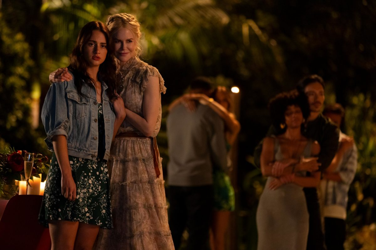 Grace Van Patten and Nicole Kidman as Zoe and Masha in 'Nine Perfect Strangers' Episode 5. Zoe stands in a denim jacket and skirt and Nicole Kidman has an arm around her shoulder and is wearing a pink dress. The rest of the group stands behind them.