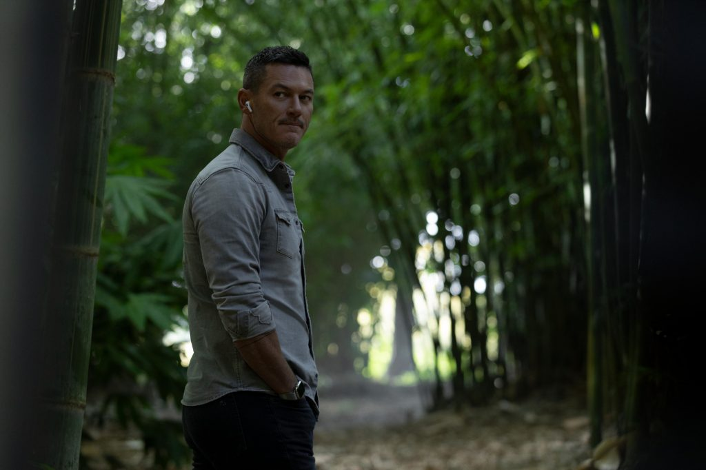 Luke Evans as Lars in Hulu's 'Nine Perfect Strangers' Episode 1. He's standing in the woods wearing a light blue button-up shirt. He has an ear piece in.