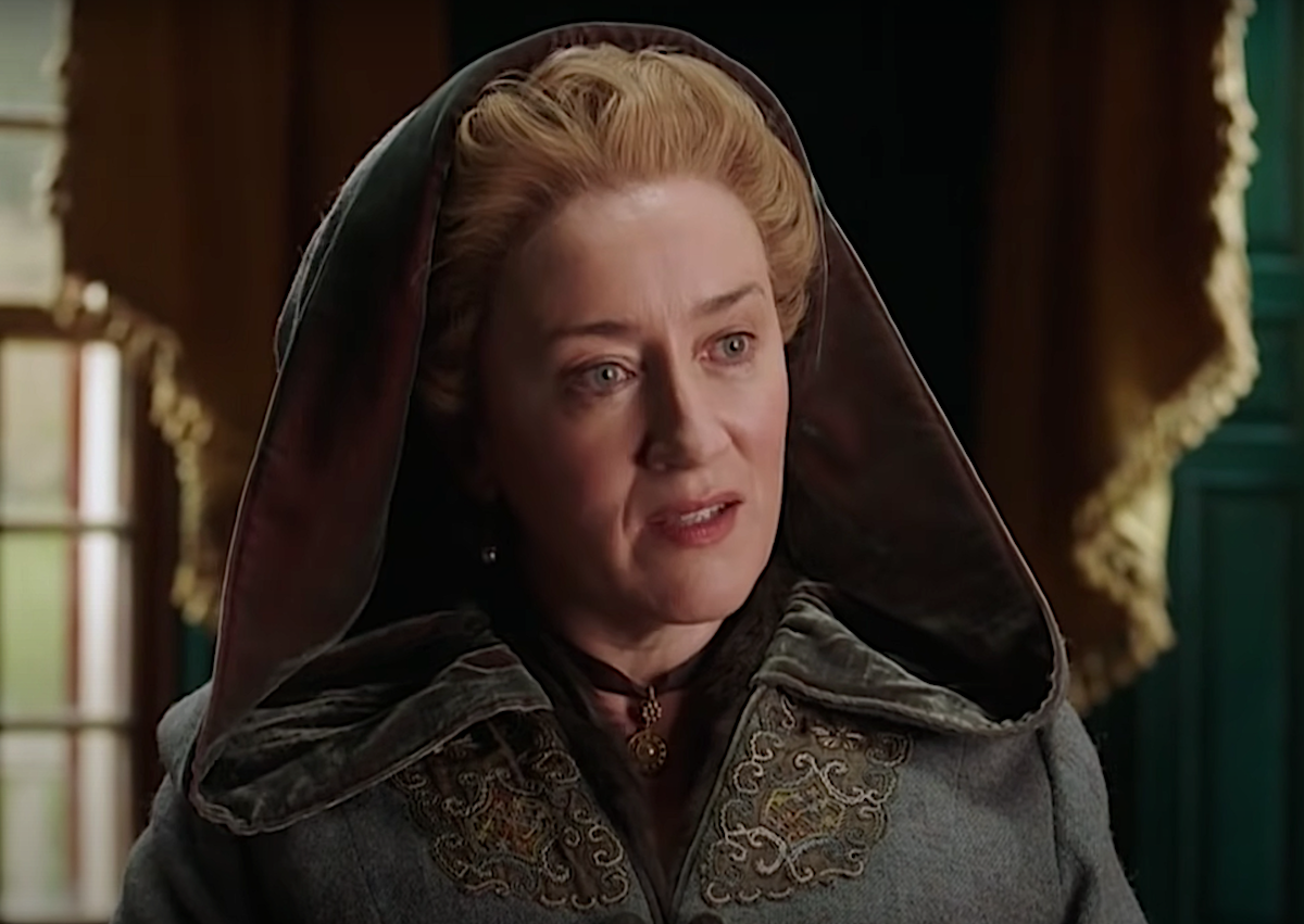 'Outlander's Maria Doyle Kennedy as Aunt Jocasta in a World 'Outlander' Day video. She wears a blue/grey colonial cloak with her hood up, a brown ribbon with a pendant around her neck. She wears a blonde wig styled in a traditional women's colonial style, and she sits in front of a window with a draping yellow curtain. Kennedy will likely return in the 'Outlander' Season 6 cast, but she could potentially not come back for season 7, which has already been green-lit by Starz.