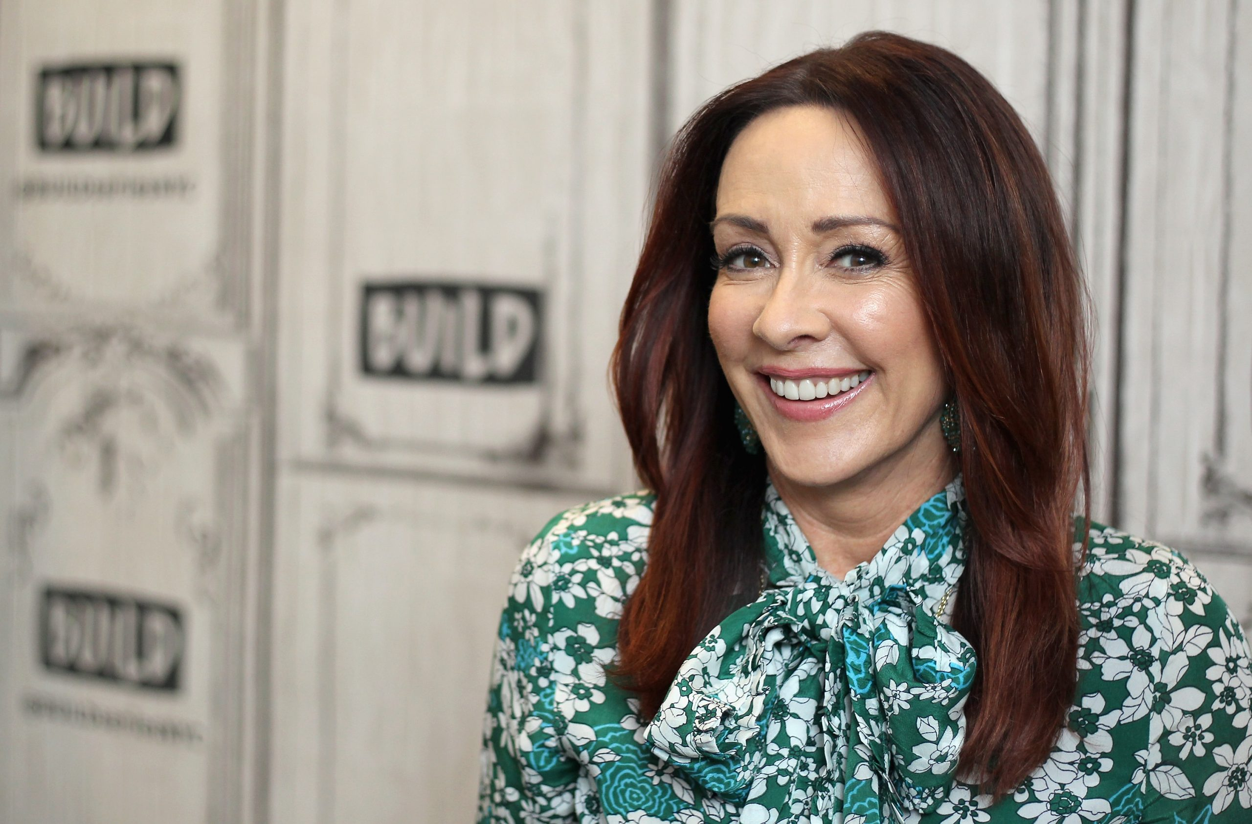 Former 'Everybody Loves Raymond' star Patricia Heaton smiles for the camera in a long-sleeved white and green print top.
