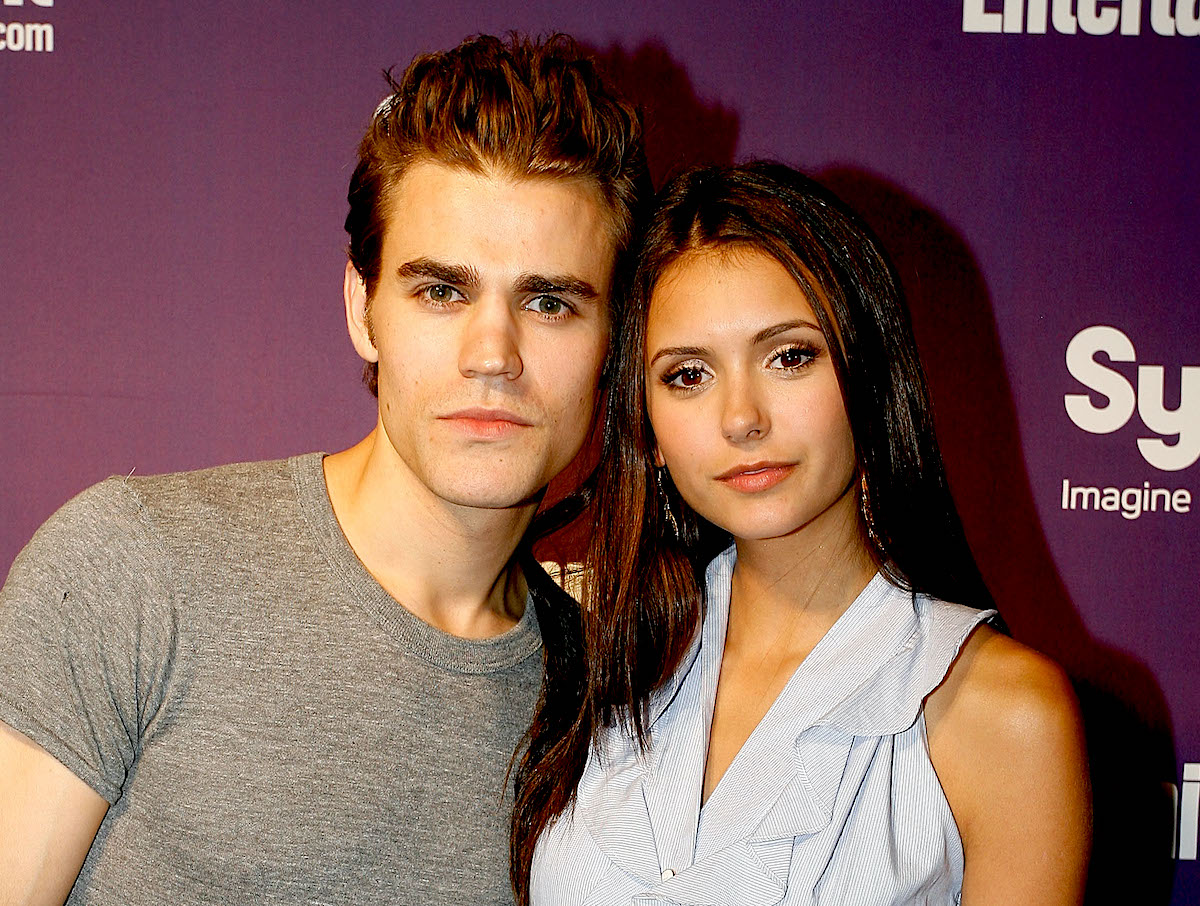 'The Vampire Diaries' stars Paul Wesley and Nina Dobrev stand closely together as they pose in front of a purple background. Wesley wears a grey T-shirt, Dobrev wears a sleeveless, collared dress that's baby blue on top and black on bottom.