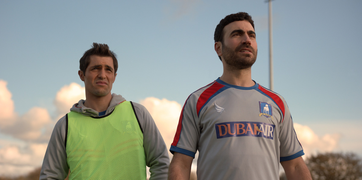 Phil Dunster as Jamie Tartt wearing a bright yellow jersey and Brett Goldstein as Roy Kent in a Richmond jersey in 'Ted Lasso'