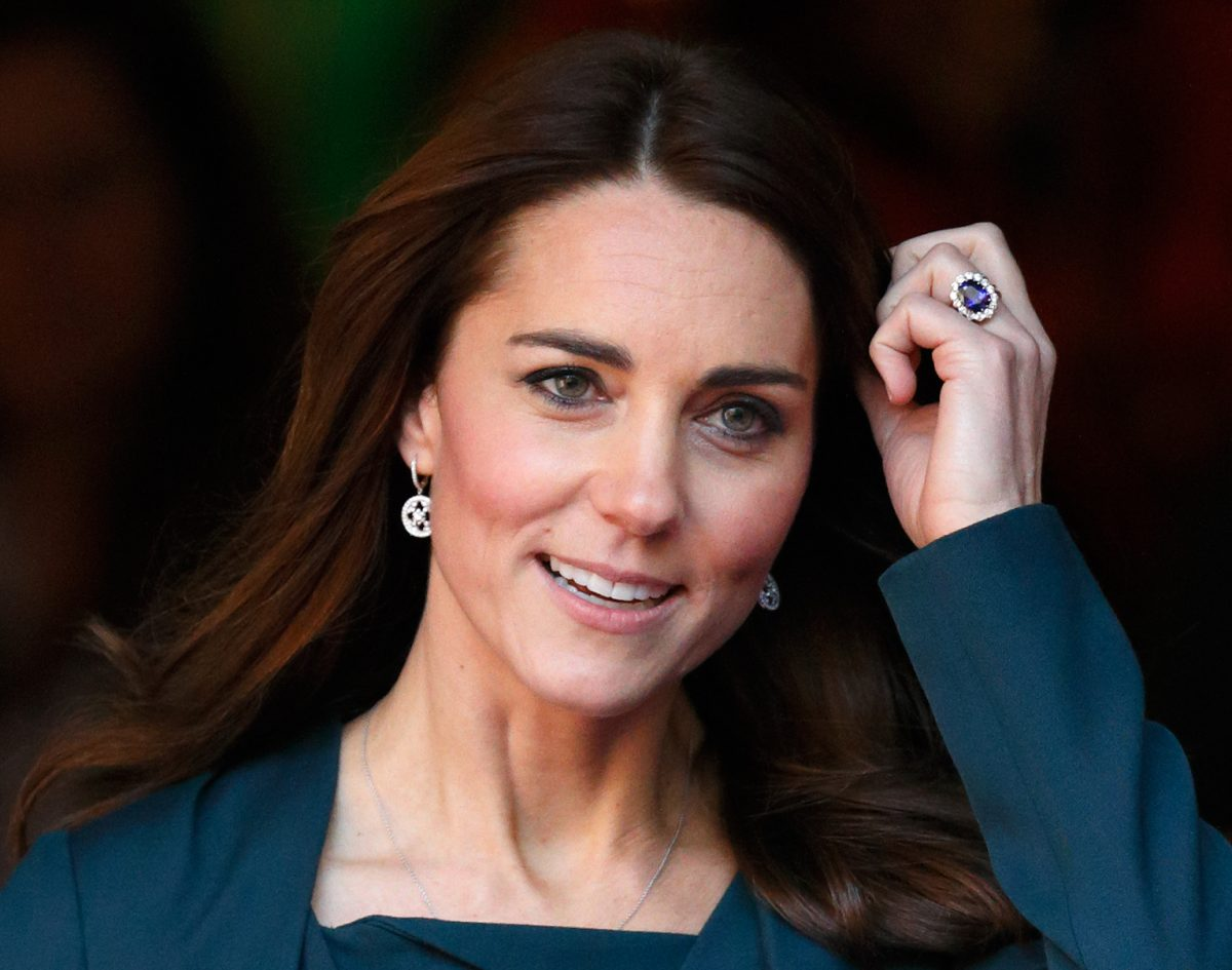 Photograph of Kate Middleton from the shoulders up poushing her hair out of her face