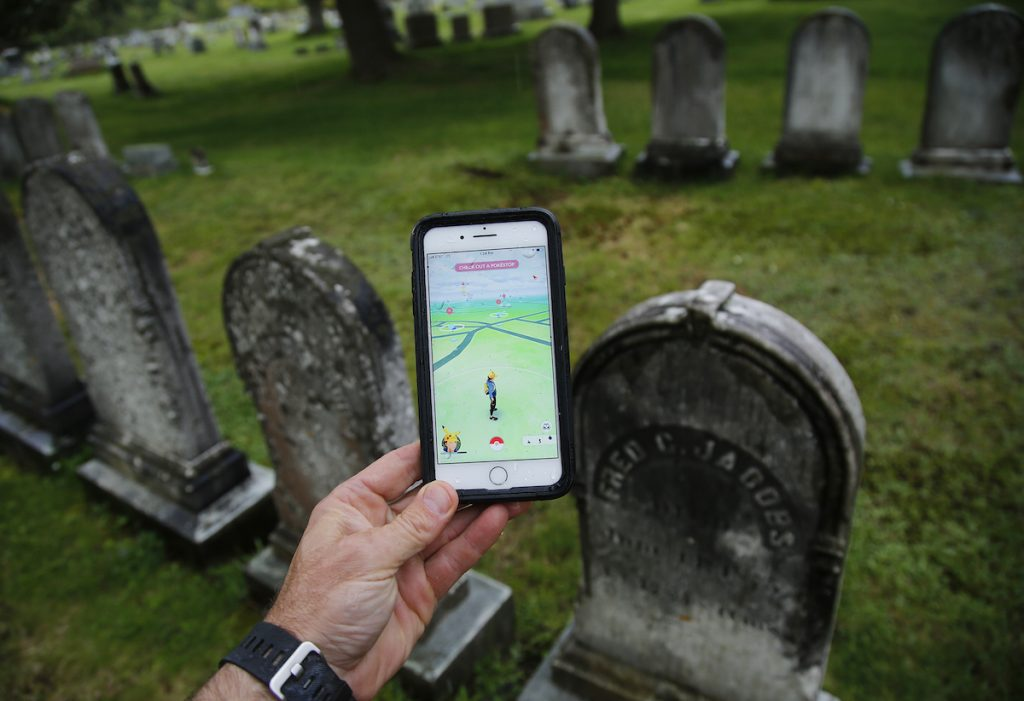 A hand holds a phone playing Pokemon Go. The background clearly shows the player is standing in a graveyard before a row of tombstones.