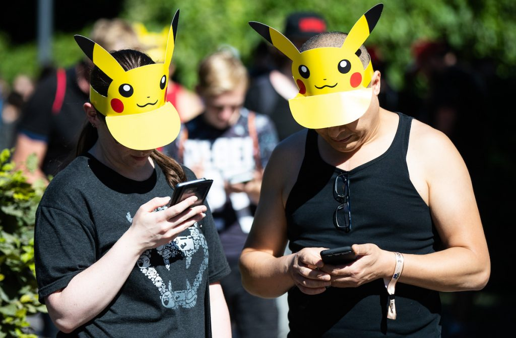 Two Pokemon Go players wearing Pikachu hats look down at their phones and play the game.