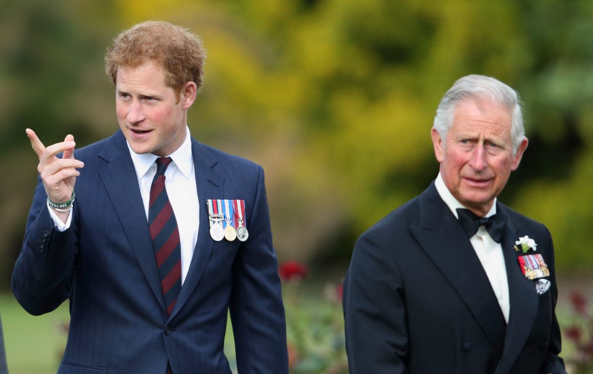 Prince Charles and Prince Harry walking together as Harry points off in the distance at Gurkha 200 Pageant