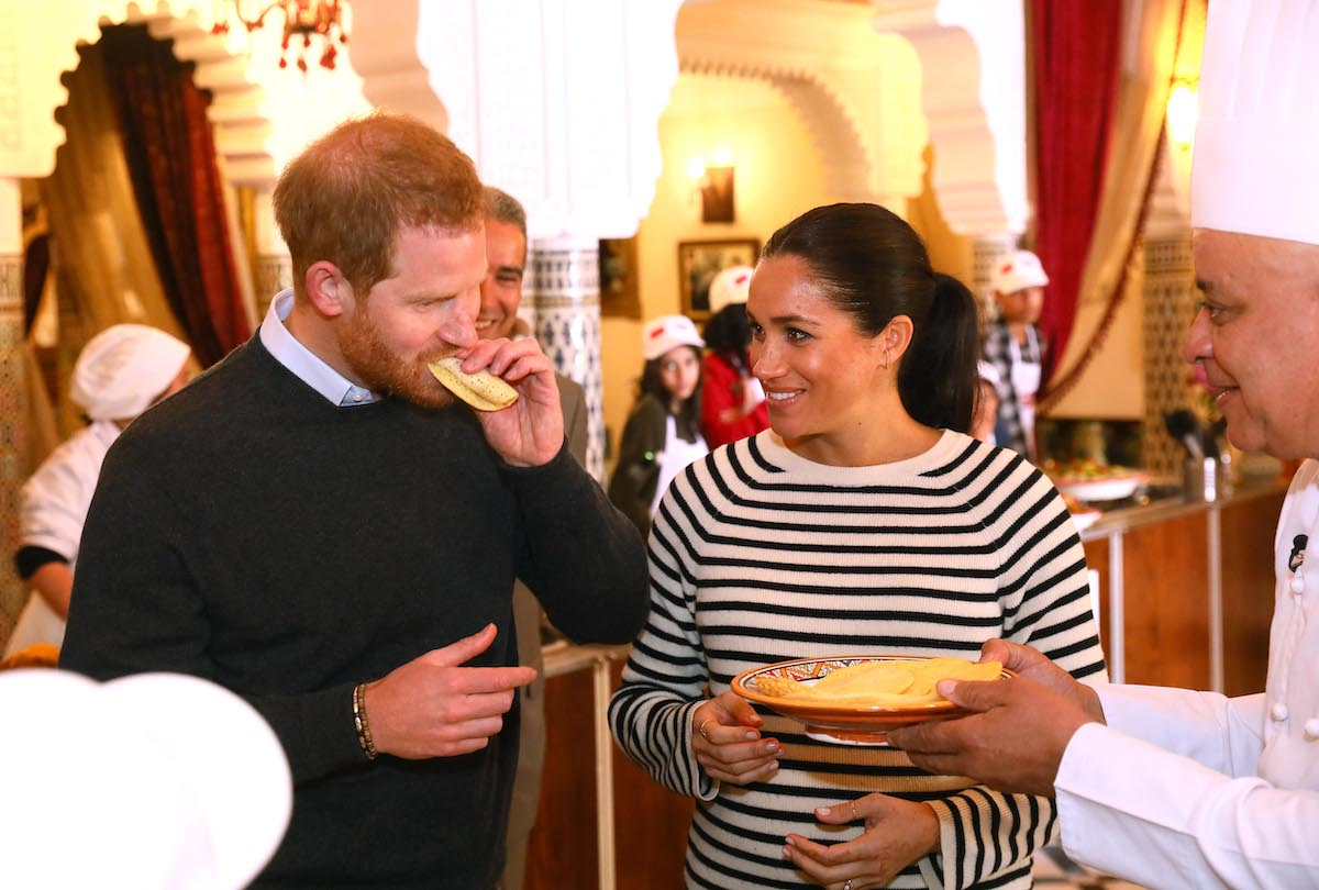 Meghan Markle smiles as Prince Harry takes a bite of food at a cooking demonstration in Morocco in 2019
