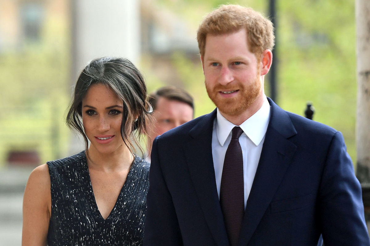 Meghan Markle in dark sleeveless top next to Prince Harry in a suit