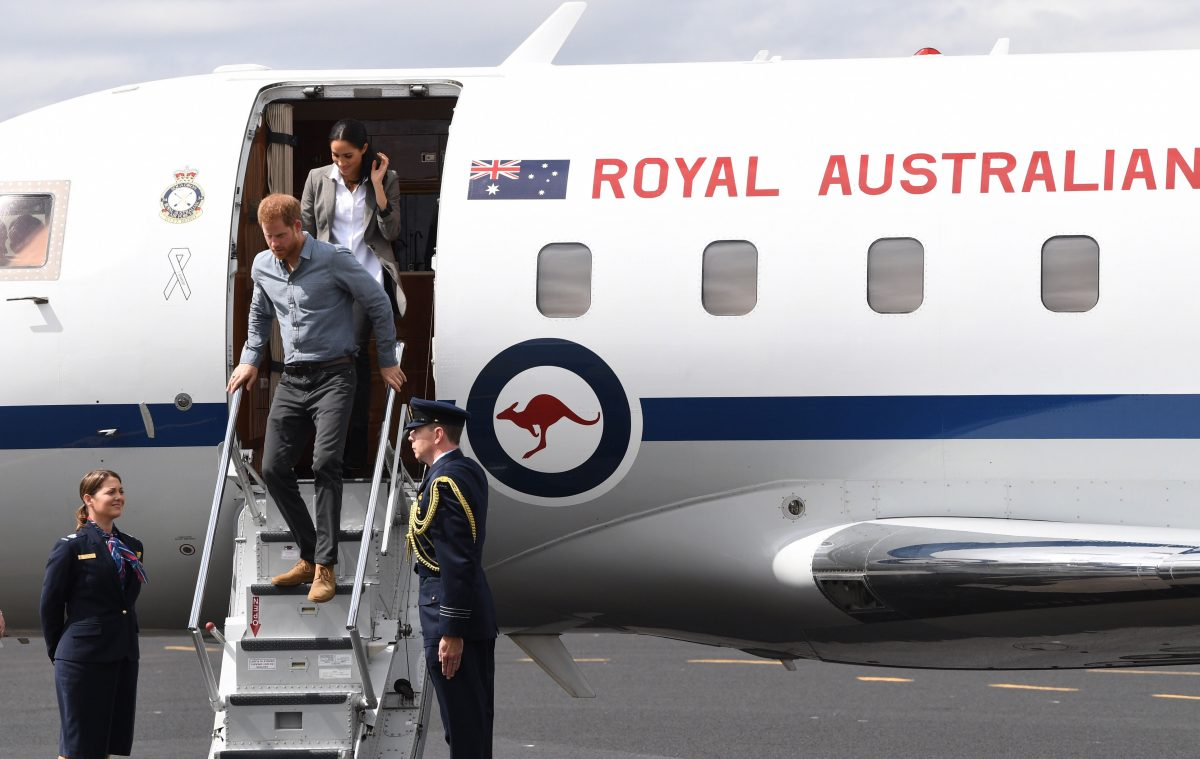 Prince Harry and his wife, Meghan Markle, disembark from their plane in Australia