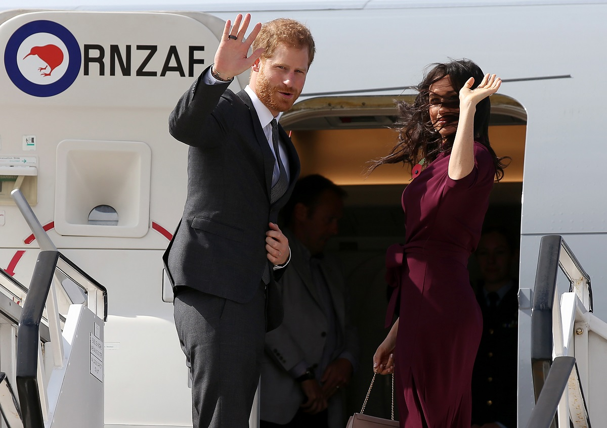 Prince Harry and his wife Meghan wave as they board aeroplane in Sydney
