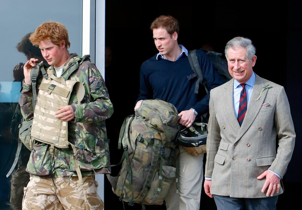 Prince Harry, carrying his rucksack as he returns from Afghanistan accompanied by Prince William and Prince Charles