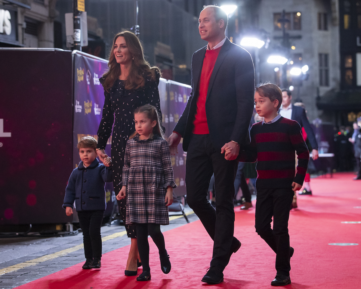 Prince William and Kate Middleton hold hands with Prince George, Princess Charlotte, and Prince Louis on the red carpet in 2020