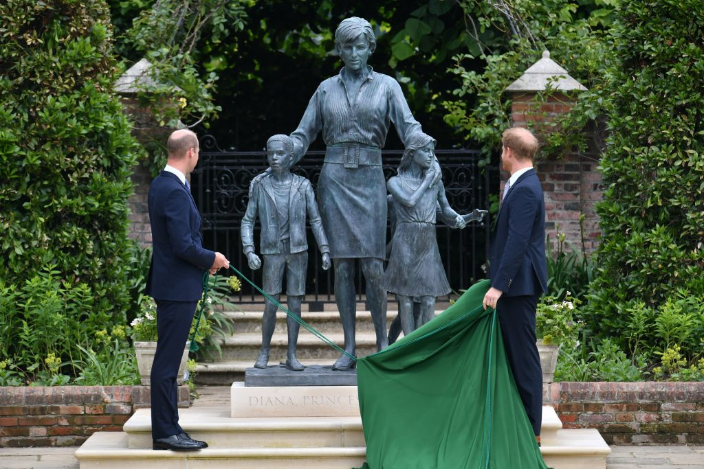 Prince William and Prince Harry wearing dark blue suits as they unveil the statue of their mother Princess Diana at Kensington Palace