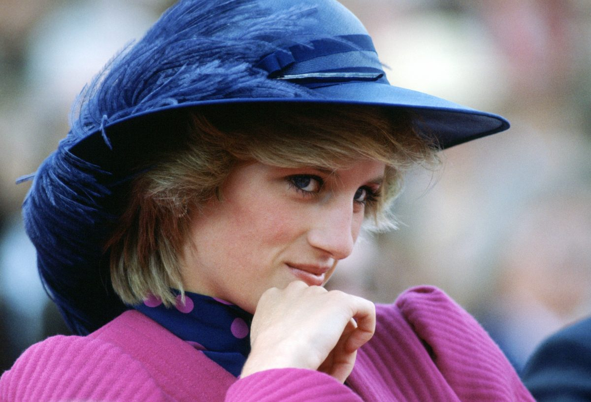 Princess Diana wearing a feathered blue hat and holding her hand up to her chin