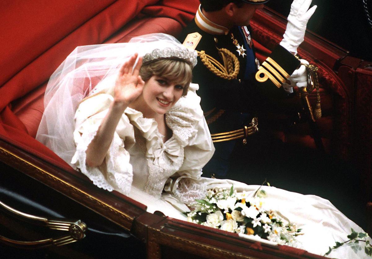 Princess Diana and Prince Charles return to Buckingham Palace by carriage after their wedding, waving to onlookers.