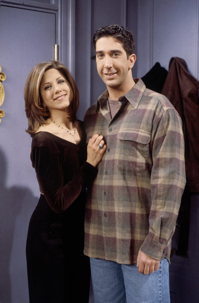 Rachel and Ross standing in Monica's apartment, facing the camera and smiling.