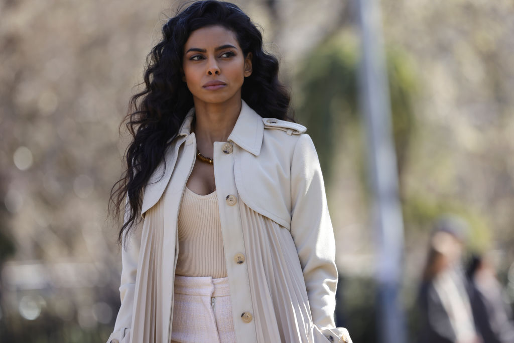 Rana Roy as Priya Laghari has a concerning look on her face as she walks through the park wearing all beige and white.