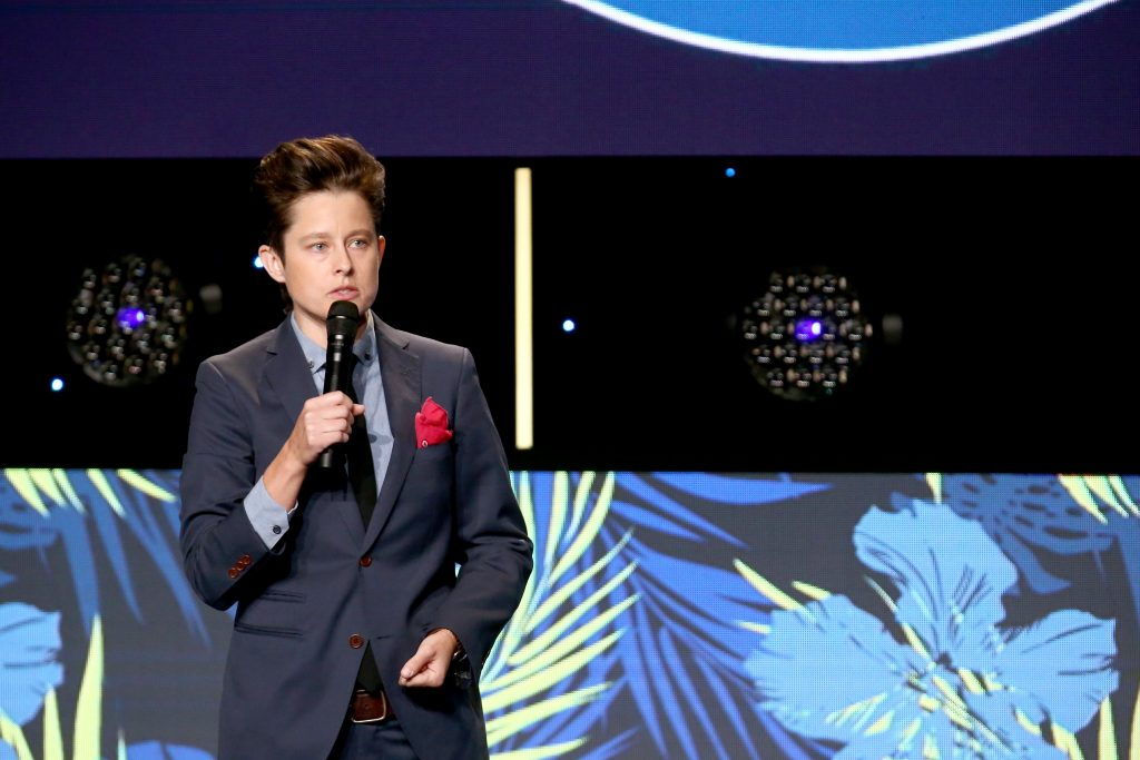 Rhea Butcher stands while holding a microphone