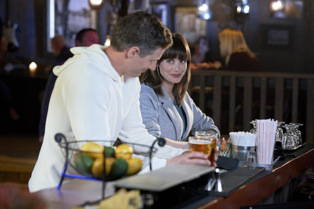 Robert Buckley and Meghan Ory sitting at a bar in 'Chesapeake Shores' Season 5