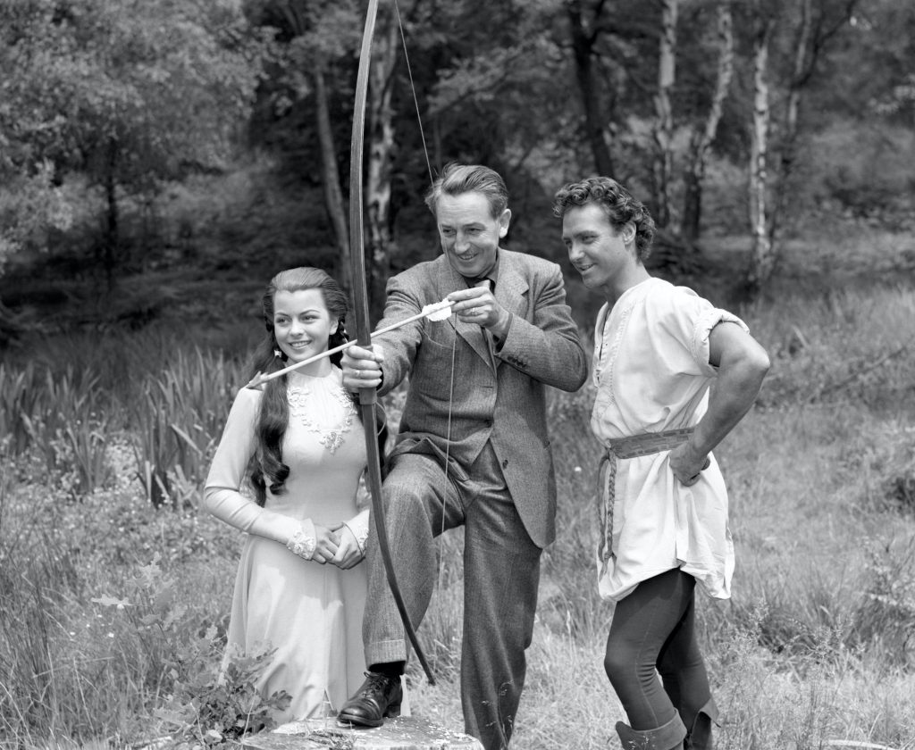 Walt Disney with 'Robin Hood' actor Richard Todd and Joan Rice, in black and white