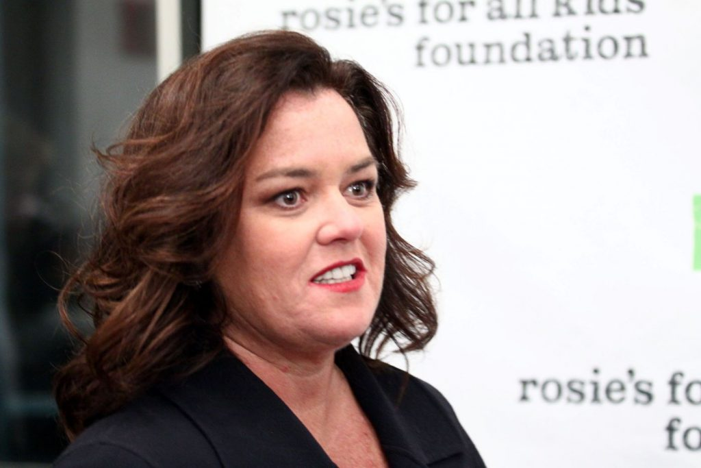 Rosie O'Donnell wearing a black jacket with a black undershirt in front of a white backdrop with black writing.