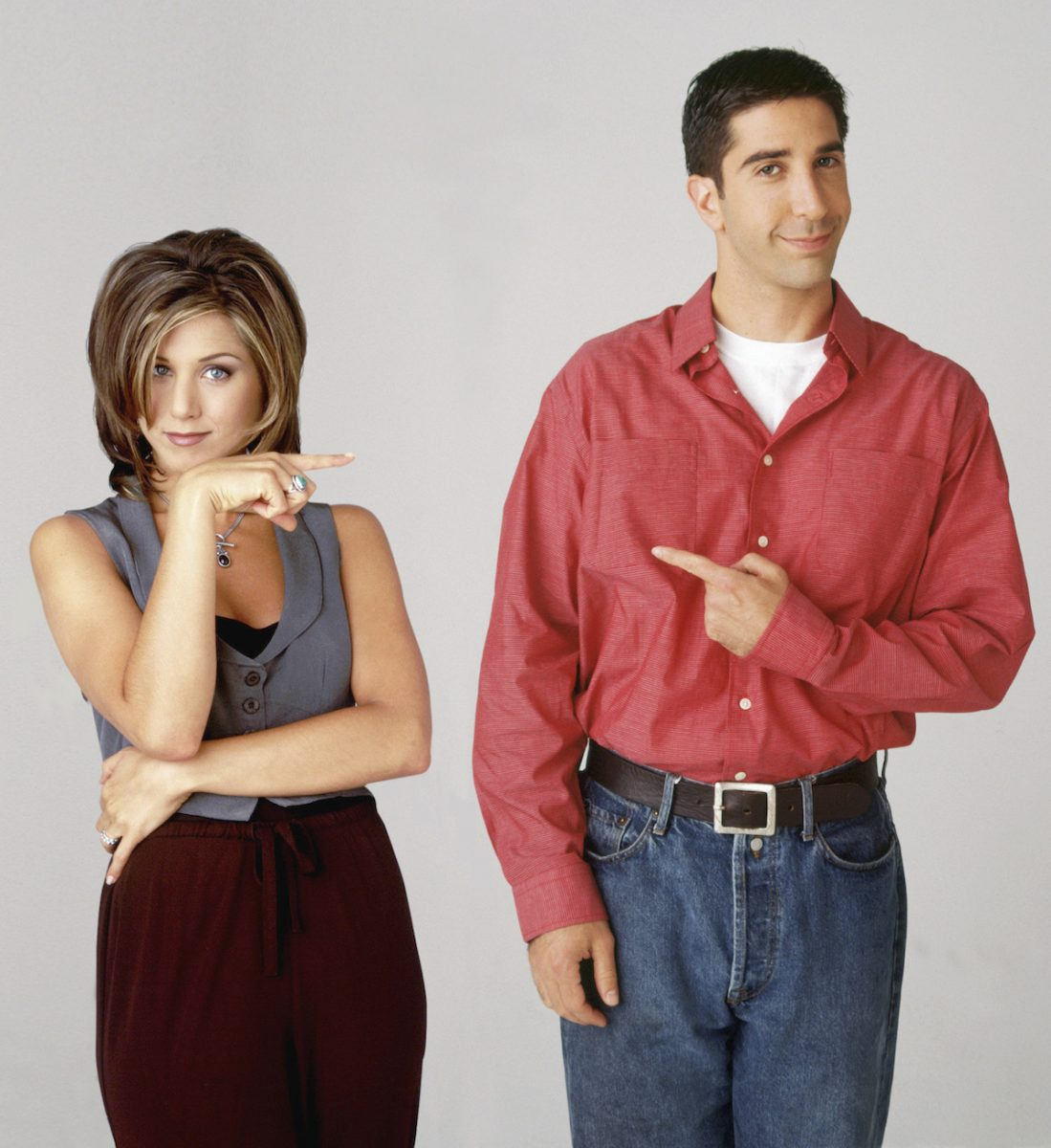 Jennifer Aniston and David Schwimmer stand facing the camera and smiling while pointing at each other.