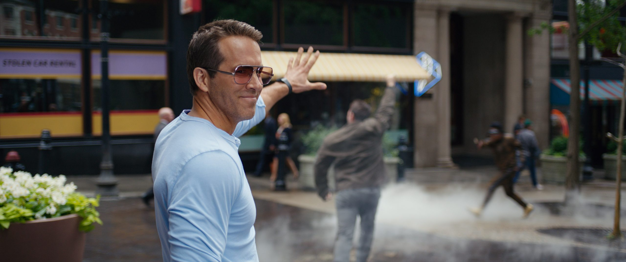 Ryan Reynolds holds his hand up in 'Free Guy'
