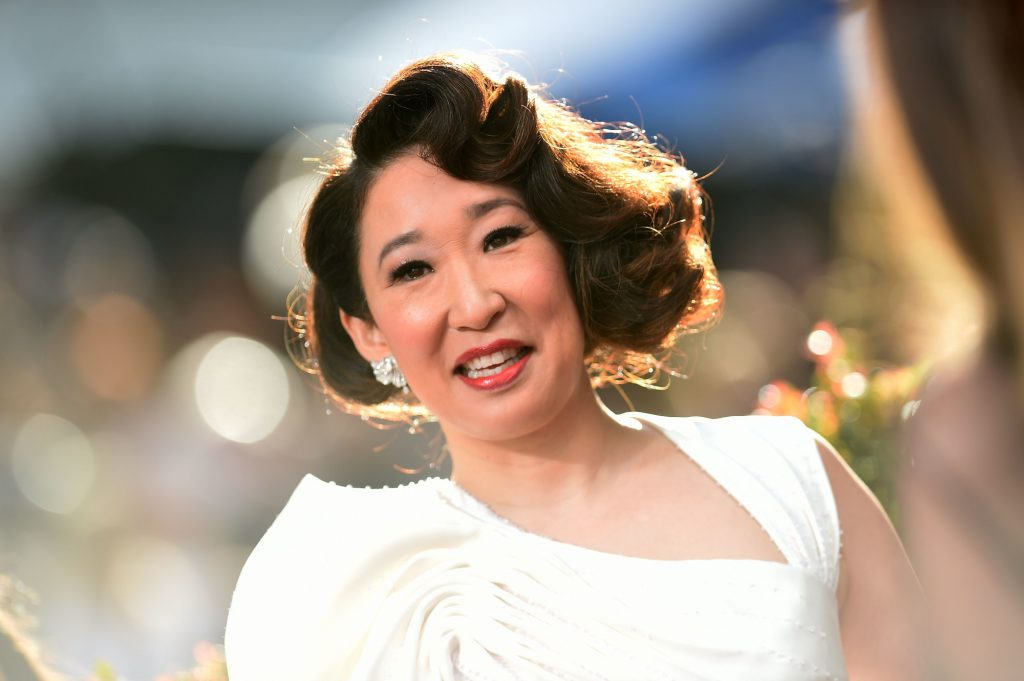 'Grey's Anatomy' star Sandra Oh wearing a white dress. Her hair is curled and she's smiling. The background behind her is blurred.