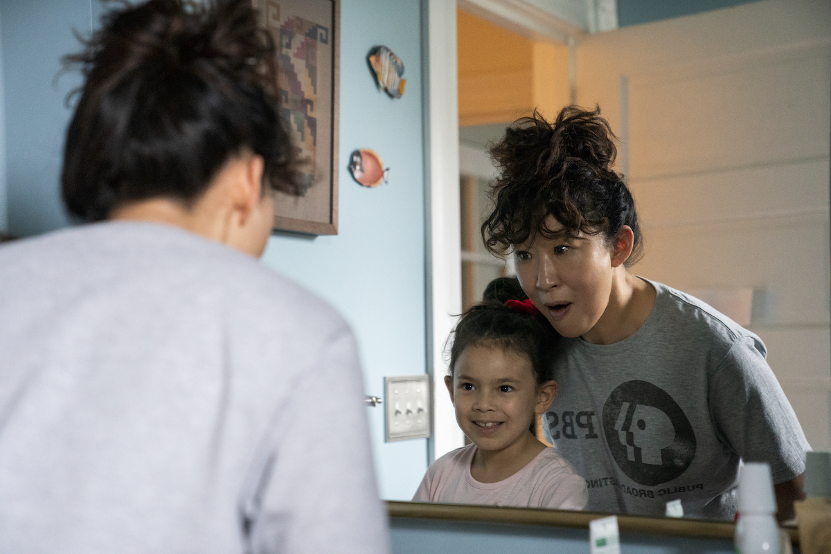 Sandra Oh wears a gray t-shirt and stands in front a bathroom mirror with Everly Carganilla in 'The Chair'